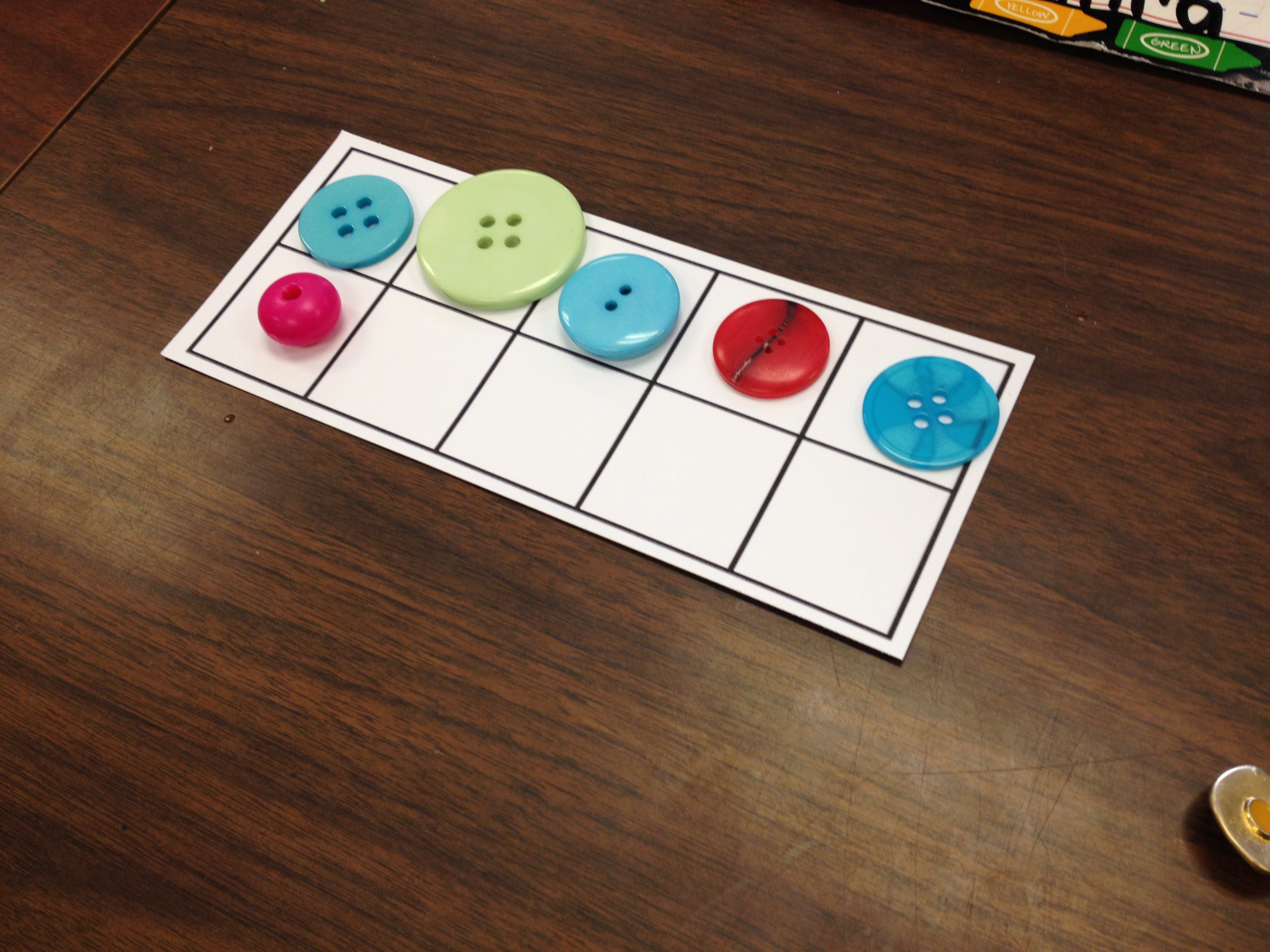 using the same ten frame mats and loose parts the students played roll it build it by rolling a regular dice simply they rolled the dice and then built